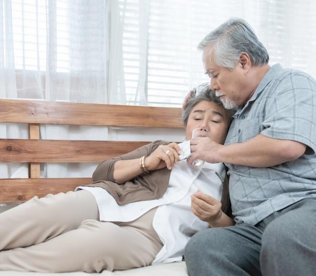 Aziatische hogere vrouw die geneesmiddelen en drinkwater nemen terwijl het zitten op laag. oude man zorgt voor zijn vrouw terwijl haar ziekte thuis. gezondheidszorg en geneeskunde concept. Premium Foto