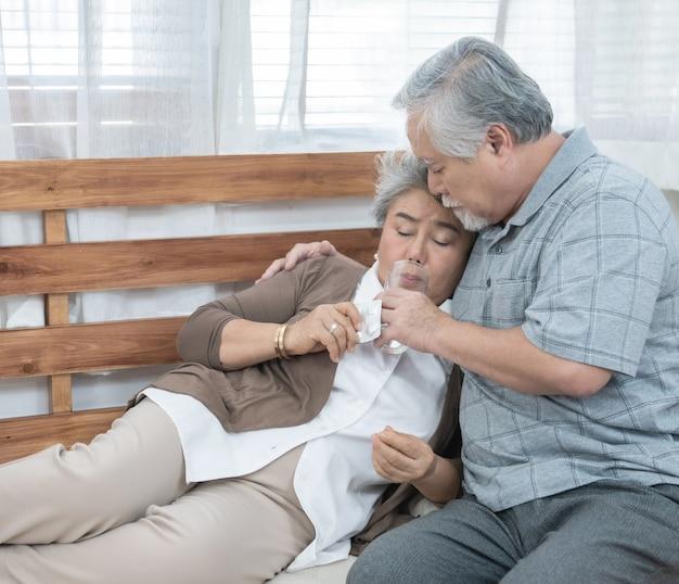 Aziatische hogere vrouw die geneesmiddelen en drinkwater nemen terwijl het zitten op laag. oude man zorgt voor zijn vrouw terwijl ze ziek is in huis. Premium Foto