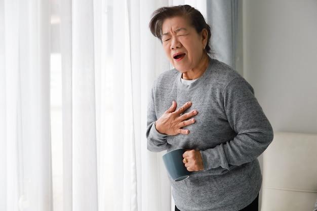 Aziatische hogere vrouwenmoeder ziek met hart attact in woonkamer Premium Foto