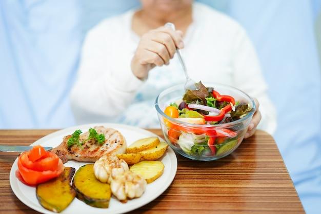 Aziatische hogere vrouwenpatiënt die ontbijt in het ziekenhuis eten. Premium Foto