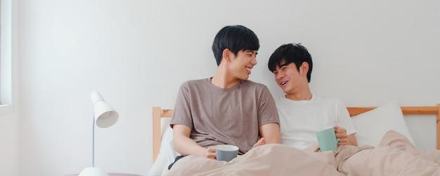 Aziatische homoseksuele mannen koppelen praten met een geweldige tijd in een modern huis. jonge aziatische minnaar lgbtq + man gelukkig ontspannen rust koffie drinken na het wakker worden terwijl liggend op bed in de slaapkamer in huis in de ochtend. Gratis Foto