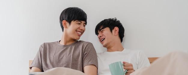 Aziatische homoseksuele mannen koppelen praten met een geweldige tijd in een modern huis. jonge de minnaar mannelijke gelukkig van azië ontspant rust drinkt koffie na kielzog omhoog terwijl het liggen op bed in slaapkamer bij huis in de ochtend. Gratis Foto