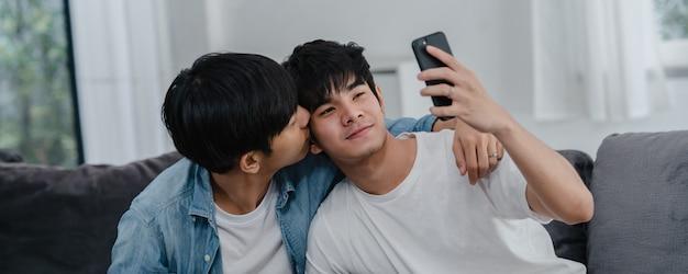 Aziatische influencer homopaar vlog thuis. aziatische lgbtq mannen gelukkig ontspannen plezier met behulp van technologie mobiele telefoon record levensstijl vlog video-upload in sociale media terwijl liggend bank in de woonkamer. Gratis Foto