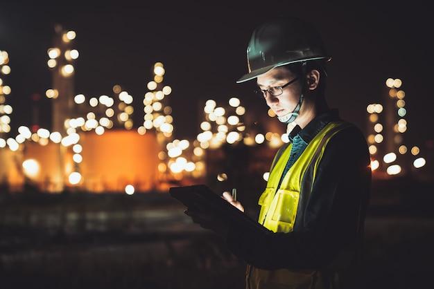 Aziatische ingenieur die digitale tablet gebruiken die laat bij olieraffinaderij werken in industrieel landgoed Premium Foto