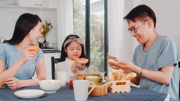Aziatische japanse familie ontbijt thuis. aziatische moeder, vader en dochter voelen zich gelukkig samen praten terwijl brood, cornflakes granen en melk in kom op tafel in de keuken in de ochtend eten. Gratis Foto