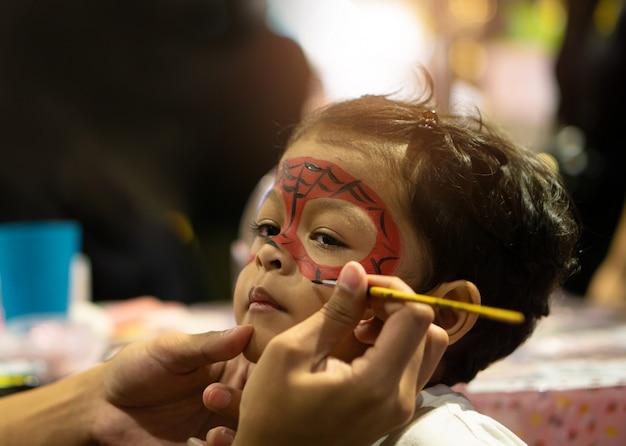 Aziatische jong geitjejongen met geschilderd gezicht als spin Premium Foto