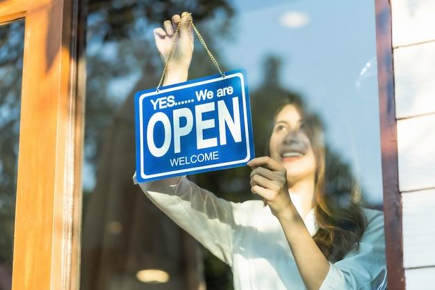Aziatische jonge aziatische vrouw die open teken plaatsen bij de winkelglazen voor welkom de klant binnen in de koffiewinkel Premium Foto