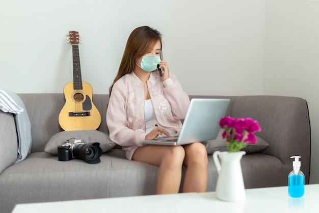 Aziatische jonge freelancervrouw die op smartphone spreken en laptop met behulp van beschermend masker dragen terwijl thuis het zitten op bank. haar handen schoonmaken met quarantaine voor ontsmettingsgel voor coronavirus. Premium Foto