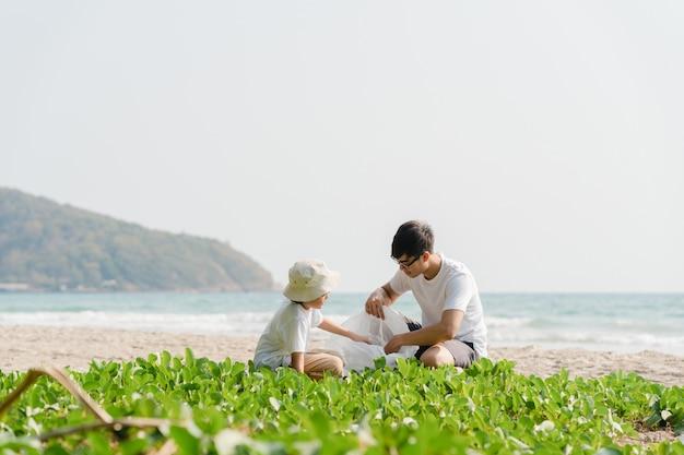 Aziatische jonge gelukkige familie-activisten die plastic afval op strand verzamelen. azië-vrijwilligers helpen de natuur schoon te houden en vuilnis op te halen. concept over milieuvervuiling problemen. Gratis Foto