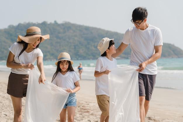 Aziatische jonge gelukkige familie-activisten die plastic afval verzamelen en op strand lopen. azië-vrijwilligers helpen de natuur afval op te ruimen. concept over milieuvervuiling problemen. Gratis Foto