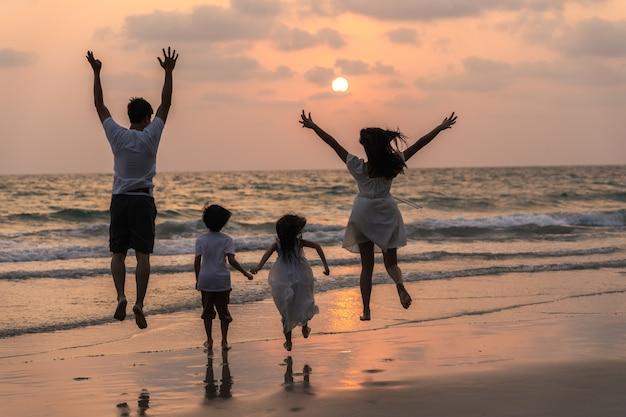 Aziatische jonge gelukkige familie genieten van vakantie op het strand in de avond. vader, moeder en kind ontspannen samen rennen in de buurt van zee terwijl silhouet zonsondergang. lifestyle reizen vakantie vakantie zomer concept. Gratis Foto