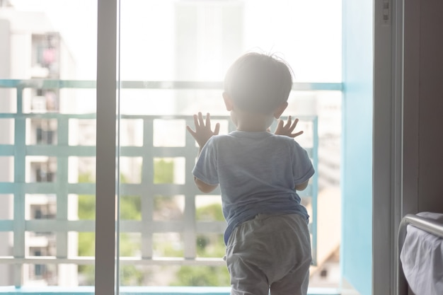 Aziatische jonge jongen die het venster opent Premium Foto