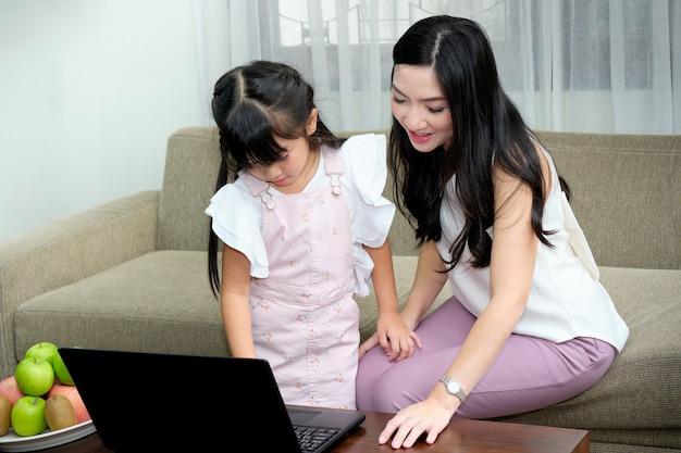 Aziatische jonge moederzitting op bank in de woonkamer met haar dochter terwijl het gebruik van laptop onderwijst Premium Foto