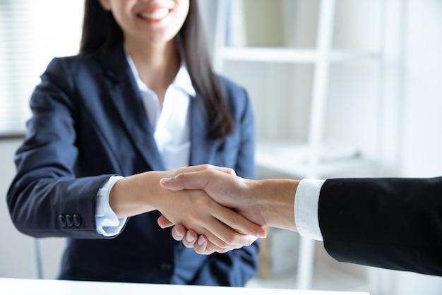 Aziatische jonge onderneemster het glimlachen handdruk met zakenmanpartner die overeenkomstenzaken samen in het het werkbureau maken Premium Foto