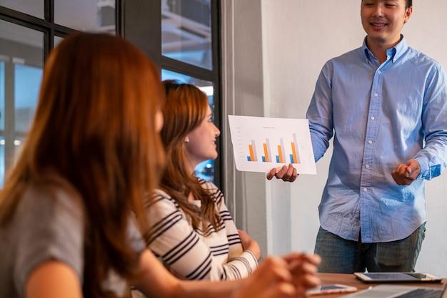 Aziatische jonge startende bedrijfsmens in vrijetijdskleding presenteert zijn werk aan collega en bespreekt en brainstormt met zijn startend commercieel team in modern co werkend bureau. een jong ondernemersconcept Premium Foto
