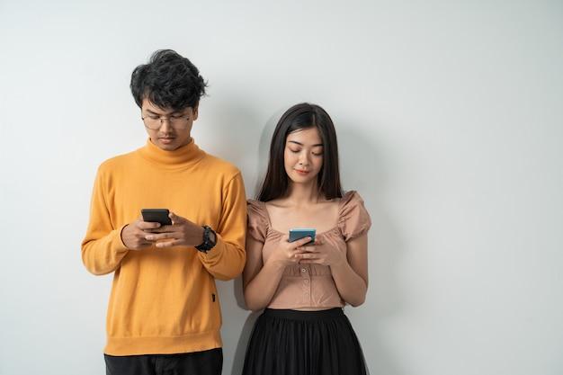 Aziatische jonge stellen gebruiken hun smartphones terwijl ze staan Premium Foto