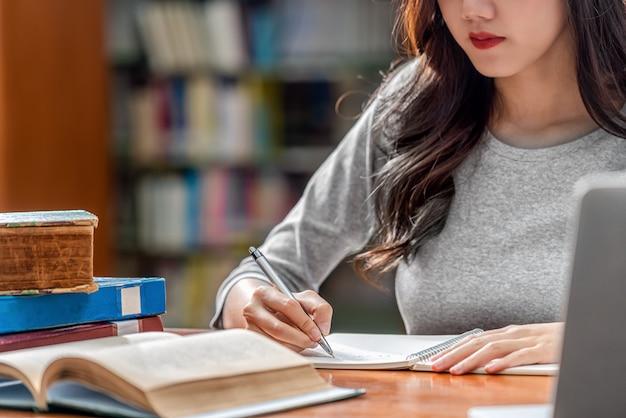 Aziatische jonge studenthand die huiswerk schrijven en technologielaptop in bibliotheek van universiteit of collega met divers boek en stationair over de boekenplank gebruiken Premium Foto
