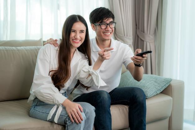 Aziatische jonge verliefde paar zitten en tv kijken en glimlachen bij het kijken naar leuk programma in tv in een comfortabele bank in de woonkamer thuis. familie levensstijl ontspannen en recreatie concept Premium Foto