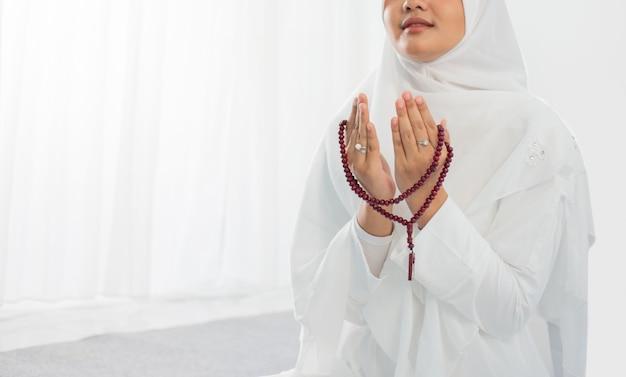 Aziatische jonge vrouw bidden met al-qur'an en gebedssnoer Premium Foto