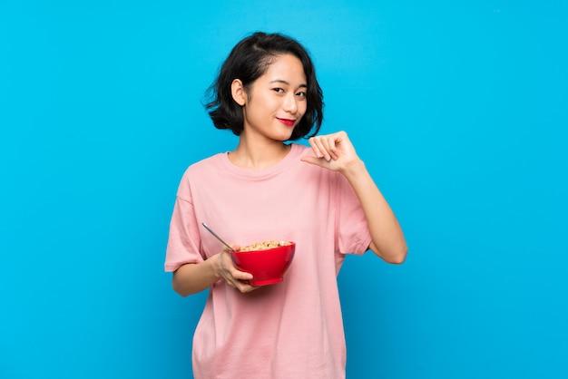 Aziatische jonge vrouw die een kom graangewassen trots en zelf-tevreden houdt Premium Foto