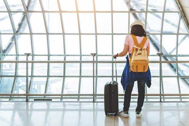 Aziatische jonge vrouw die met koffer en gele rugzak op de vlucht bij venster van de luchthaven wacht. Premium Foto