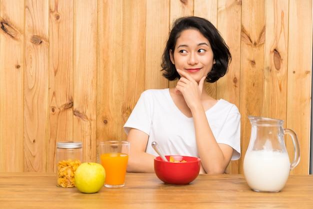 Aziatische jonge vrouw die ontbijtmelk heeft die een idee denkt Premium Foto