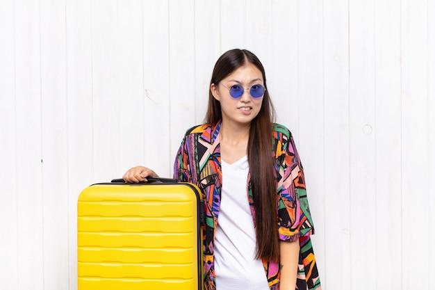 Aziatische jonge vrouw die verbaasd en verward kijkt, lip bijt met een nerveus gebaar, het antwoord op het probleem niet weet. vakantie concept Premium Foto