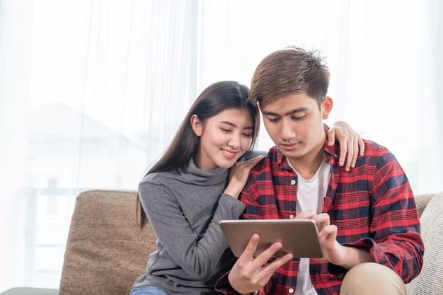 Aziatische jonge vrouw en knappe man zittend op de bank met behulp van apparaat Gratis Foto
