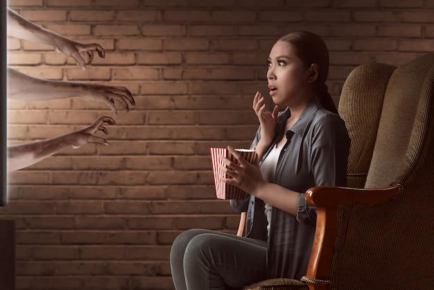 Aziatische jonge vrouw horrorfilm kijken en eet de popcorn met zittend op de bank Premium Foto