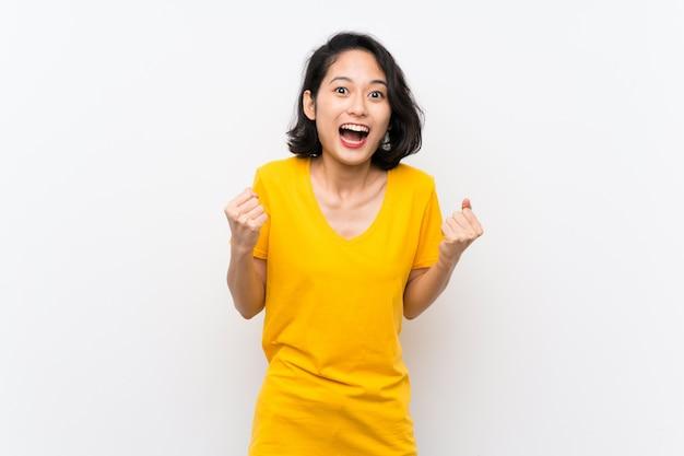 Aziatische jonge vrouw over geïsoleerde witte achtergrond die een overwinning in winnaarpositie viert Premium Foto
