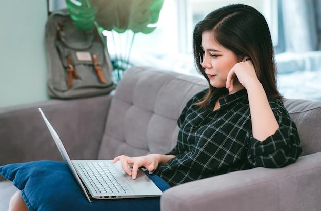 Aziatische jonge vrouw thuis blijven om te ontspannen met winkelen en tv-kijken thuis woonkamer. werk vanuit huis en blijf thuis concept Premium Foto