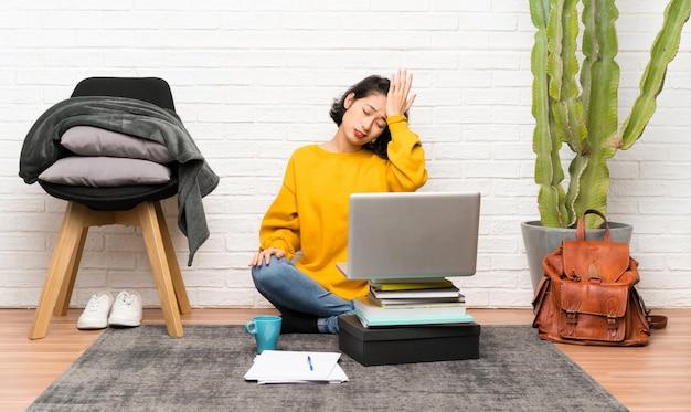 Aziatische jonge vrouw zittend op de vloer met twijfels met verwarren gezichtsuitdrukking Premium Foto