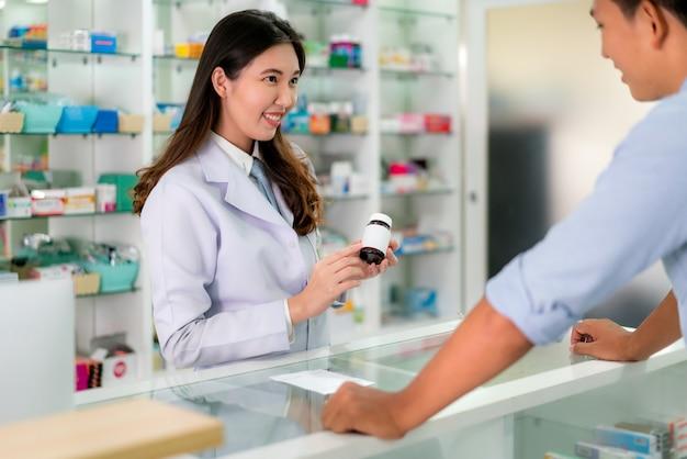 Aziatische jonge vrouwelijke apotheker met een mooie vriendelijke glimlach en uitleggen geneeskunde aan haar klant in de apotheek drogisterij. Premium Foto