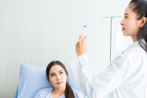 Aziatische jonge vrouwelijke arts met spuit naar aziatische jonge vrouwelijke patiënt op bed voor betere genezing in het ziekenhuis Premium Foto