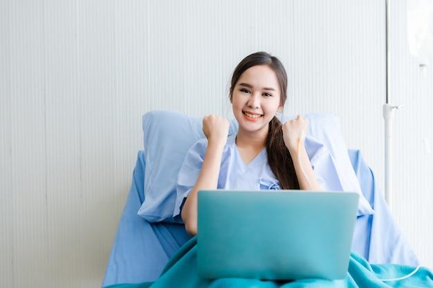 Aziatische jonge vrouwelijke patiënt uitgedrukt vertrouwen aangemoedigd op bed en laptop computer in het kamerziekenhuis Premium Foto
