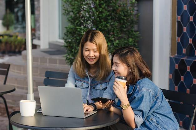 Aziatische jonge vrouwen in slimme vrijetijdskleding die e-mail op laptop en het drinken koffie werken terwijl Gratis Foto