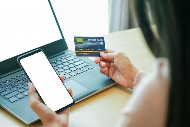 Aziatische jonge vrouwenhanden die creditcard houden en laptop smartphone met behulp van Premium Foto