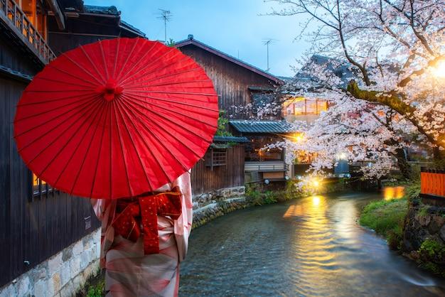 Aziatische jonge vrouwenreiziger die japanse traditionele kimono met rode paraplu dragen die bij de beroemde bloesem van de bestemmingskers bij shirakawa-rivier in het gion-district bij nacht in kyoto, japan bezienswaardigheden bezoeken. Premium Foto