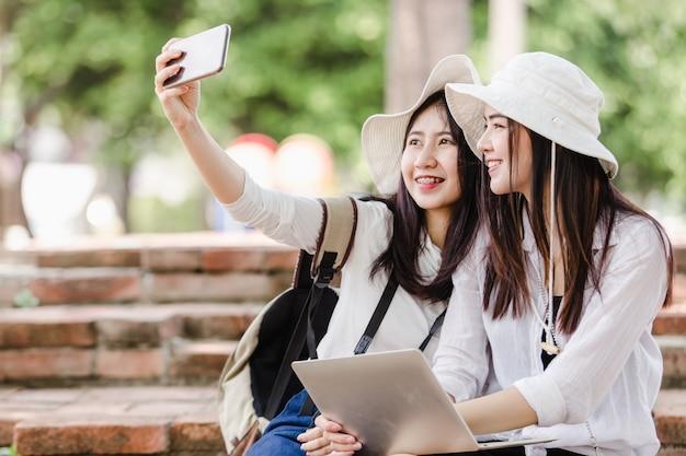Aziatische jonge vrouwentoeristen die een selfie in stad nemen Premium Foto