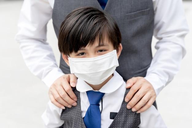 Aziatische jongen die beschermend gezichtsmasker draagt ter bescherming tijdens de uitbraak van quarantaine coronavirus covid 19 Gratis Foto