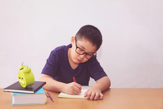 Aziatische jongen die een boek op lijst schrijft Premium Foto