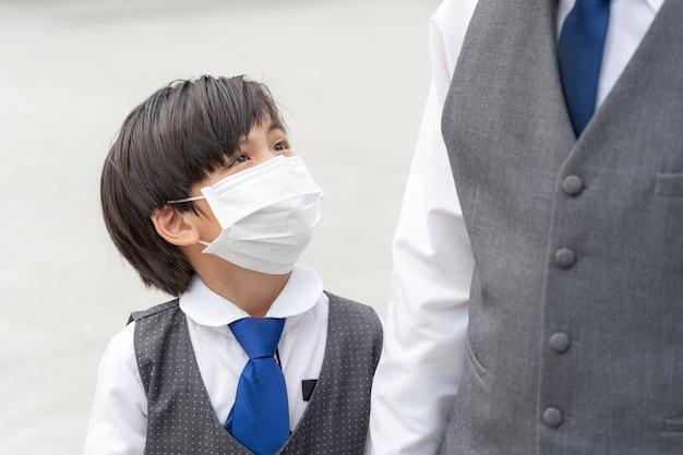 Aziatische jongen die gezichtsmasker draagt, verspreidt covid-19 coronavirus, aziatische familie die gezichtsmasker draagt voor bescherming Gratis Foto