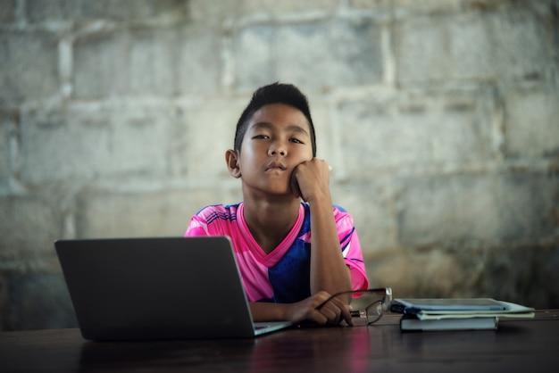 Aziatische jongen die laptop op de lijst gebruikt, komt terug naar school Gratis Foto