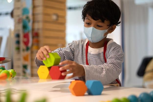 Aziatische jongen dragen gezichtsmaskers om het coronavirus 2019 (covid-19) te voorkomen en spelen speelgoed op scholen. Premium Foto