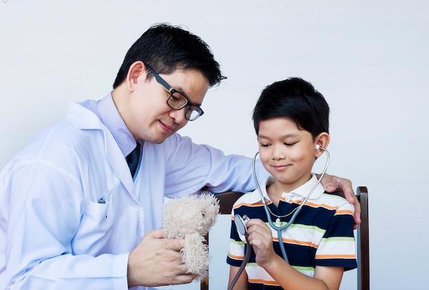 Aziatische jongen en arts tijdens het onderzoeken van het gebruiken van stethoscoop over witte achtergrond Gratis Foto