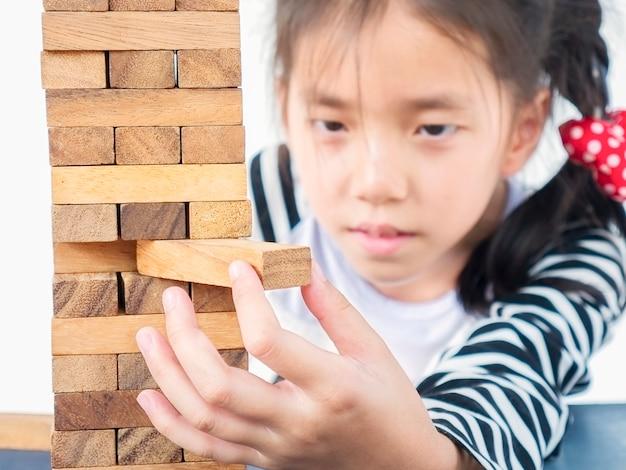 Aziatische jongen speelt jenga, een houten blokken torenspel voor het beoefenen van fysieke en mentale vaardigheden Gratis Foto