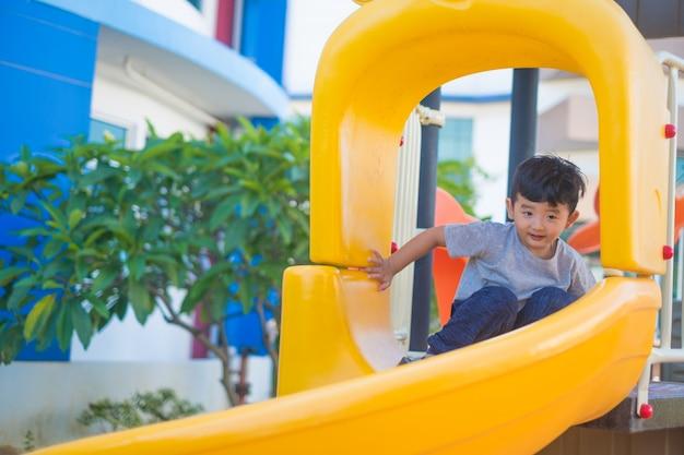 Aziatische jongen spelen dia op de speelplaats onder het zonlicht in de zomer, gelukkig kind in de kleuterschool of voorschoolse schoolplein. Premium Foto