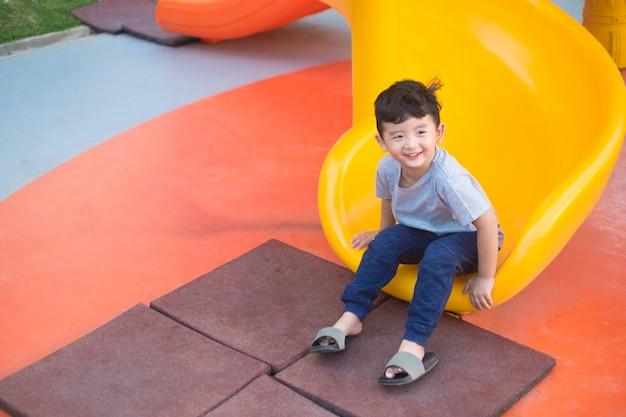 Aziatische jongen spelen dia op de speelplaats Premium Foto
