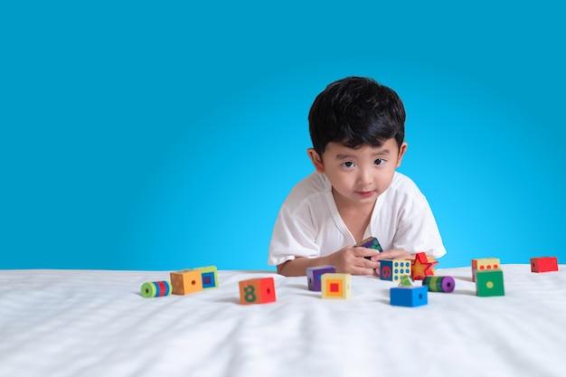 Aziatische jongen spelen vierkante blok puzzel thuis op het bed Premium Foto