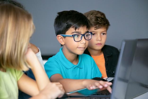 Aziatische jongen typen op laptop toetsenbord en klasgenoten aan tafel zitten, kijken naar hem en samen taak doen Gratis Foto